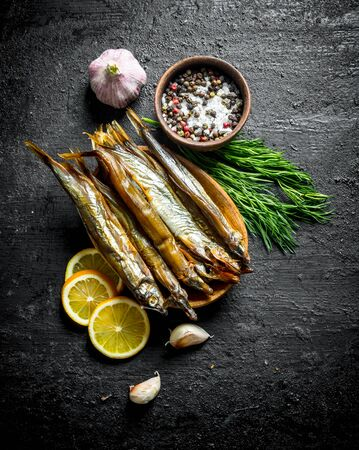 Smoked fish with lemon slices, dill, garlic and spices. On black rustic background