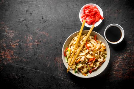 Delicious noodles with ginger and soy sauce. On dark rustic background