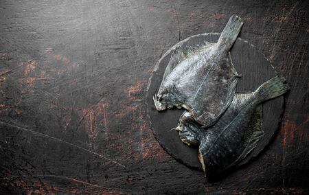 Raw fish flounder on a stone Board. On dark rustic background