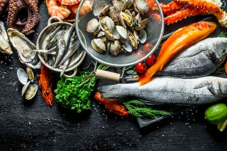 Variety of fresh seafood with herbs and lime. On black rustic background