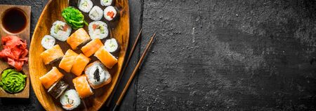 Set of different sushi rolls with ginger, soy sauce and wasabi. On black rustic background