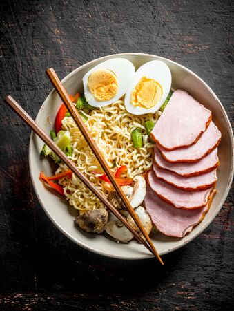 Delicious noodles with becon, mushrooms and cut egg. On dark rustic background Stock Photo