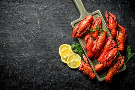Delicious Boiled crayfish on a cutting Board with sliced lemon and dill. On black rustic background Stok Fotoğraf