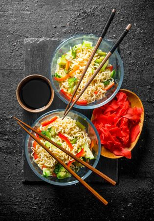 Instant noodles with vegetables in glass bowls on a stone Board. On black rustic background Stock Photo