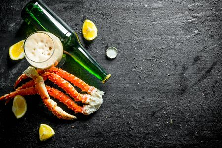 Crab with lemon slices and beer. On black rustic background Stock Photo