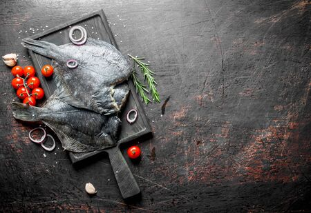 Raw fish flounder on a cutting Board with cherry tomatoes and sliced onions. On dark rustic background Banque d'images