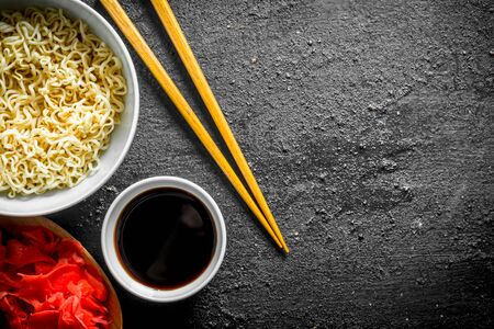 Instant noodles with soy sauce and ginger. On black rustic background Stock Photo
