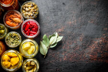 Various preserved food in jars with Bay leaf. On dark rustic background Stock Photo - 124761736