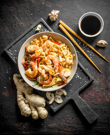 Noodles in a plate on a cutting Board with ginger and soy sauce. On dark rustic background