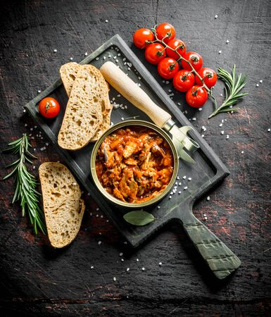 Open tin can with sprat in tomato sauce on the cutting Board. On dark rustic background Stock fotó