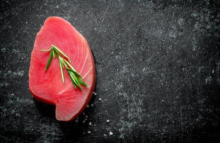 Piece of raw tuna with rosemary. On dark rustic background Stok Fotoğraf