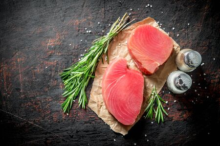 Raw tuna fillet on paper with rosemary and spices. On dark rustic background