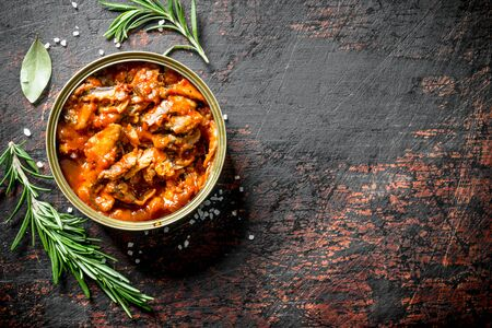 Sprat in tomato sauce with rosemary. On dark rustic background