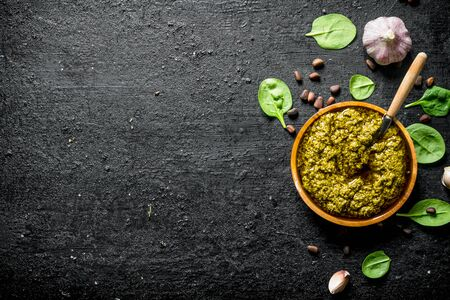 Pesto sauce with Basil, garlic and pine nuts. On black rustic background