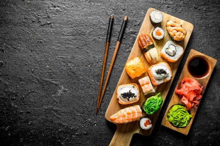 Variants of types of sushi, rolls and maki on a cutting Board with sticks. On black rustic background Stockfoto
