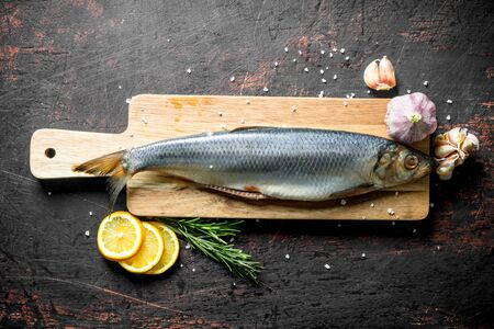 Salted herring with lemon slices, garlic and rosemary. On dark rustic background