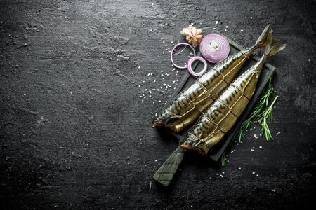 Smoked mackerel on a cutting Board with rosemary, onion rings and garlic. On black rustic background