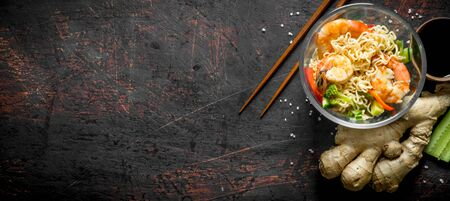 Instant noodles with vegetables, shrimp and fresh ginger. On dark rustic background
