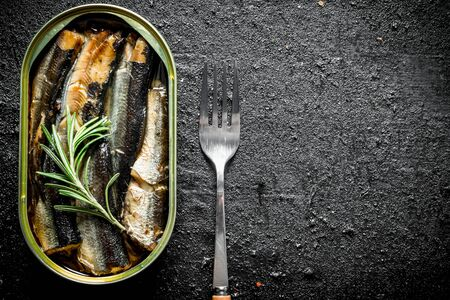 Fragrant sprats in a tin can. On black rustic background Stok Fotoğraf