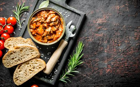 Sprat in tomato sauce with bread and tomatoes on the cutting Board. On dark rustic background