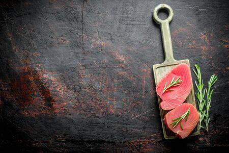 Fresh raw tuna steak on a cutting Board with rosemary. On dark rustic background Stok Fotoğraf