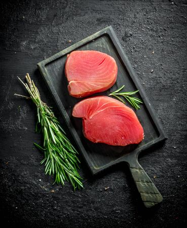 Pieces of raw tuna on a cutting Board with a bunch of rosemary. On black rustic background Stok Fotoğraf