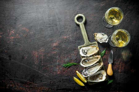 Raw oysters on a cutting Board with two glasses of white wine. On dark rustic background