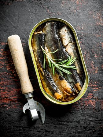 Open tin can with sprats. On dark rustic background