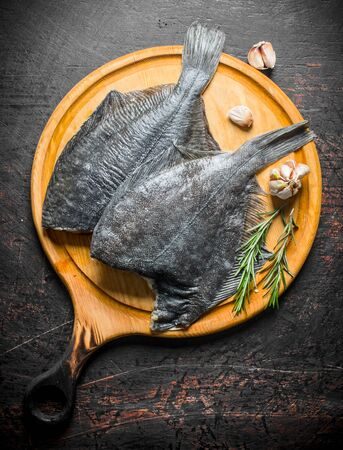 Raw fish flounder on a wooden cutting Board with garlic and rosemary. On dark rustic background Stok Fotoğraf