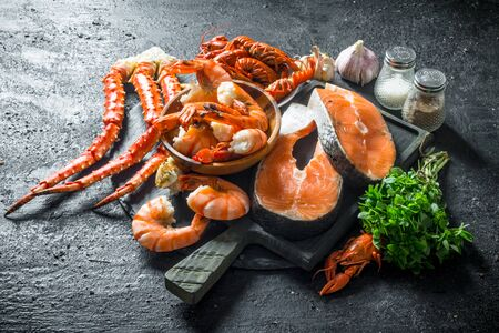 Fresh fish steak on a chopping Board with boiled shrimp, crayfish and crab. On black rustic background 写真素材