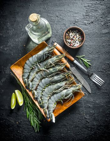 Raw shrimps with lime slices, rosemary and spices. On black rustic background