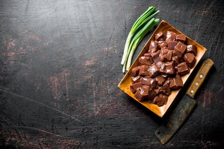 Pieces of raw liver on a wooden plate with green onions. On dark rustic background