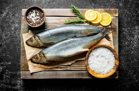 Salted herring on a wooden tray with lemon slices, rosemary and spices. On dark rustic background Stok Fotoğraf
