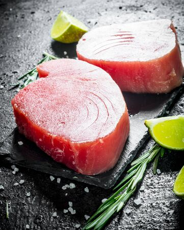 Raw tuna fillet on a stone Board with pieces and lime. On black rustic background
