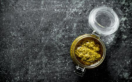 Pesto sauce in a glass jar. On dark rustic background