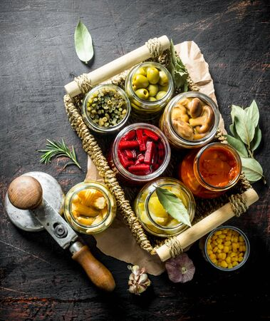 Homemade pickled vegetables in jars on the tray. On dark rustic background