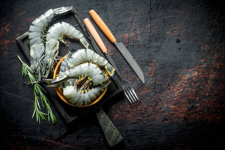 Raw shrimps on a cutting Board with sprigs of rosemary. On dark rustic background