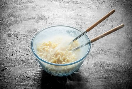 Heated instant noodles in glass bowl with chopsticks. On black rustic background Stock Photo