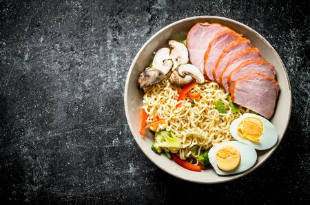 Instant noodles in bowl with broccoli, mushrooms, becon and egg. On dark rustic background