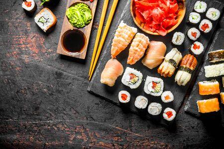 Fresh sushi rolls on black stone stand. On dark rustic background Stockfoto