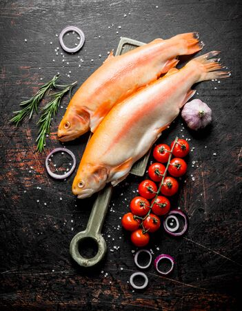 Raw trout fish with onion rings, tomatoes, rosemary and garlic. On dark rustic background Stok Fotoğraf