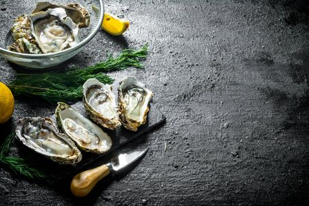 Fresh raw oysters on a stone Board and in a colander with lemon and dill. On black rustic background