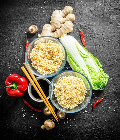 Instant noodles with ginger, mushrooms, bell peppers, Peking cabbage and soy sauce. On black rustic background Stock Photo