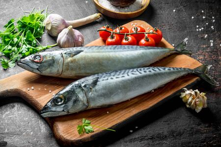 Fresh raw fish mackerel on a cutting Board with tomatoes, herbs and garlic cloves. On dark rustic background