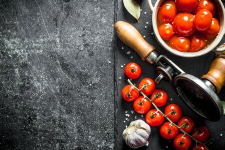 Pickled tomatoes in a bowl and a branch of fresh tomatoes. On dark rustic background Фото со стока