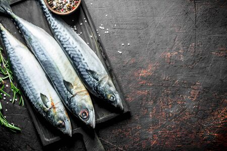 Raw fish mackerel on a cutting Board with rosemary and spices. On dark rustic background