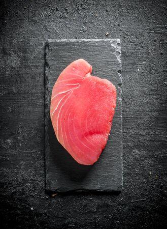 Raw tuna steak on a stone Board. On black rustic background