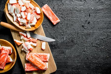 Pieces of crab sticks on a wooden cutting Board with a knife. On black rustic background Stok Fotoğraf - 124763378