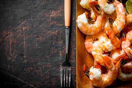 Fragrant shrimps on a wooden plate with a fork. On dark rustic background Stok Fotoğraf - 124763379