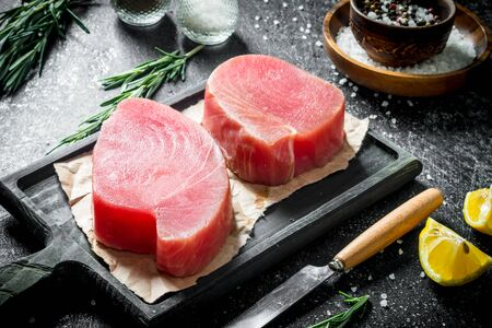 Raw tuna fillet on a cutting Board with spices and rosemary. On dark rustic background Stock Photo